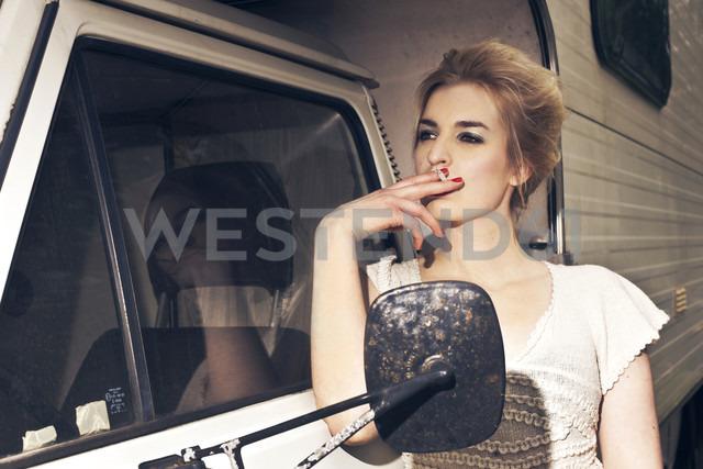 Germany, Berlin, Young woman smoking next to camping bus - NG000010