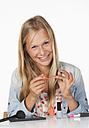 Teenage girl applying nail polish, close up - WWF002474