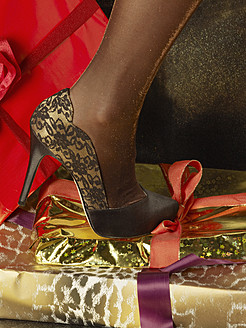 Human leg in high heels steps on wrapped christmas presents - BSCF000219