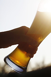 Germany, Bavaria, Human hand holding wheat beer glass, close up - JTF000267