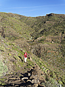 Spain, La Gomera, Mature woman hiking through Barranco de Charco Hondo - SIEF003162