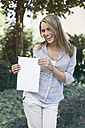 Germany, Duesseldorf, Young woman holding folder, smiling, portrait - MF000460