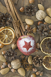 Christmas apple with snow star, hazelnuts, walnuts, almonds, star anise, cinnamon sticks, dried orange slice and pine cones on table - ASF004749