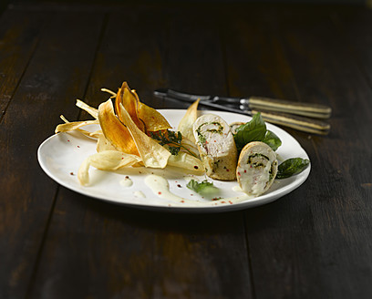 Plate of chicken roulade with chips on wooden table, close up - KSW001014