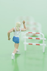 Figurine woman running in front of hurdles - ASF004765