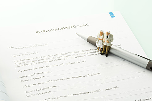 Figurines standing on pen with advance directive form, close up - MAEF005544