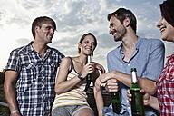 Germany, Berlin, Men and women having fun on roof terrace, smiling - RBF001185
