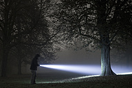 Germany, Munich, Young man with torch in foggy night - FL000181