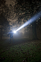 Germany, Munich, Man lighting spooky tree with torch in foggy night - FL000153