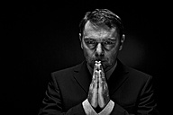 Mature man in full suit praying against black background, close up - MAE005686