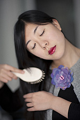 Young Japanese woman combing her hair, close up - FL000195