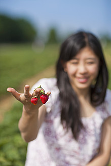 Germany, Bavaria, Young Japanese woman holding strawberries - FLF000207
