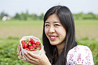 Germany, Bavaria, Young Japanese woman picking strawberries in field - FLF000216