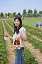 Germany, Bavaria, Young Japanese woman picking strawberries in field - FLF000220