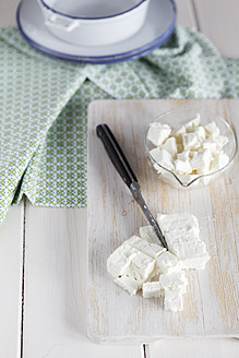 Feta cheese with knife on chopping board, close up - EVGF000049