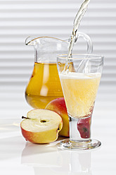 Apple juice being poured into glass besides apples and pitcher - CSF016394