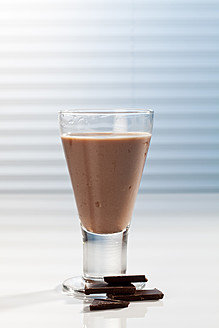 Glass of chocolate milk and pieces of chocolate, close up - CSF016428