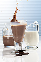 Glass and carafes of chocolate milk and pieces of chocolate, close up - CSF016431