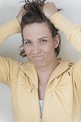 Germany, North Rhine Westphalia, Bonn, Portrait of woman tearing her hair - KJF000198