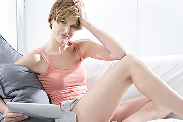 Young woman using digital tablet on couch, portrait - MAEF005760