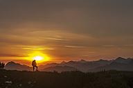 Austria, Salzburg Country, Man hiking through Niedere Tauern mountains at sunrise - HHF004303