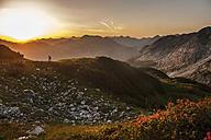 Austria, Salzburg Country, Man hiking through Niedere Tauern mountains at sunrise - HHF004305