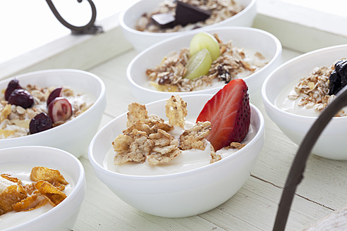 Bowls of yogurt with muesli and fruits on wooden tray - CSF016552