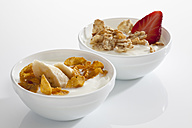 Bowls of yogurt with flakes, muesli, banana and strawberry on white background, close up - CSF016561