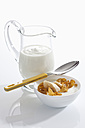 Bowl of muesli yogurt with banana beside yogurt carafe on white background, close up - CSF016567
