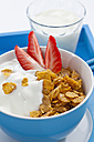 Bowl of cornflower with strawberries and glass of milk on white background - CSF016600