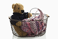 Basket with teddy bear and knitting yarn on white background, close up - CSF016615
