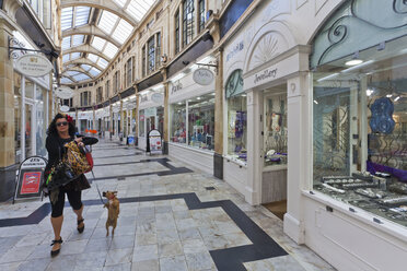 England, Sussex,  Worthing, Woman with dog walking at Royal Arcade - WD001584