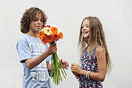 Netherlands, Boy giving flowers to girl in front of wall, smiling - MIZ000230