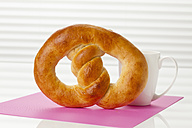 Sweet pretzel with cup of coffee, close up - CSF016820