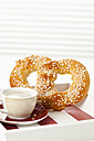Sweet pretzel with cup of coffee, close up - CSF016823