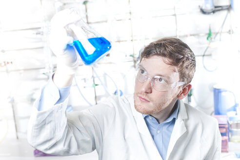 Germany, Young scientist checking blue liquid in erlenmeyer flask - FLF000230