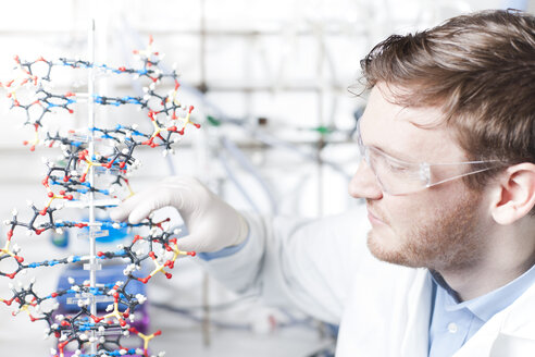Germany, Young scientist with DNA model - FLF000242