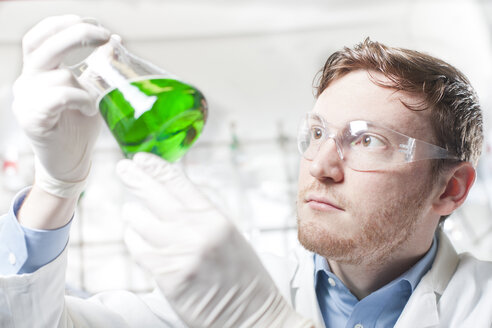 Germany, Young scientist checking green liquid in erlenmeyer flask - FLF000244