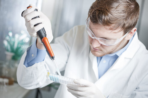 Germany, Young scientist pipetting blue liquid into 96 well plate - FLF000249
