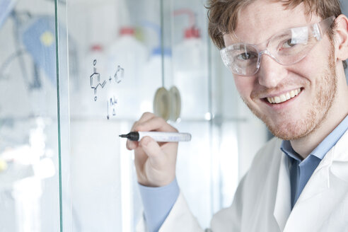 Germany, Portrait of young scientist writing chemical equation on glass, smiling - FLF000289