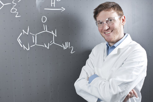 Germany, Portrait of young scientist standing next to chemical equation on chalk board, smiling - FLF000298