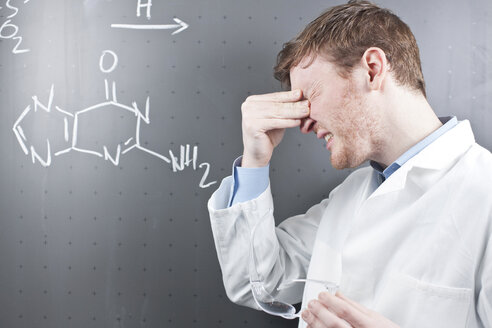 Germany, Young scientist with serious facial expression and chemical equation on chalk board - FLF000300