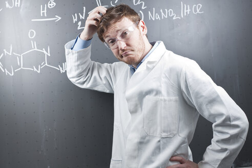 Germany, Young scientist with pluzzled facial expression and chemical equation on chalk board - FLF000301