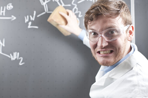 Germany, Young scientist erasing chemical equation on chalk board - FLF000304