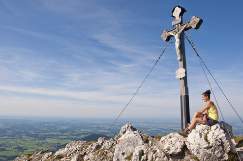 Germany, Bavaria, Mid adult woman sitting on mountain summmit with cross - UMF000591