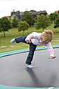 Germany, Kiel, Girl jumping on trampoline - JFE000016
