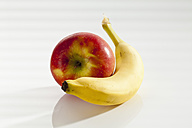 Banana with apple on white background, close up - CSF017515