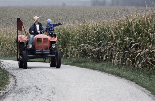 Austria, Farmer and his son driving tractor on road in middle of corn field - CW000012