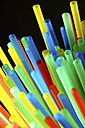 Assortment of colorful drinking straws on black background - HOHF000073