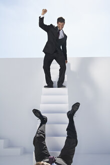 Businessman standing on stairs and other one falling down - PDYF000385